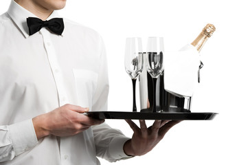 Waiter hands champagne in bucket and stemware on tray