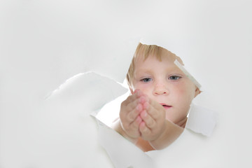 cute child looking out through hole in paper