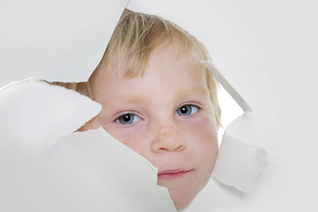 cute child looking out from hole in paper