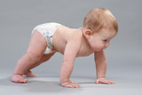 Little boy in pampers crawling