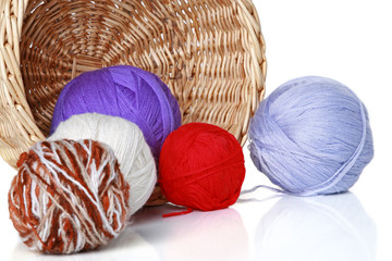 multi-colored balls of yarn in wicker basket