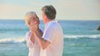 Mature couple dancing on a beach