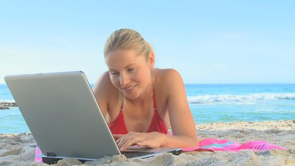Woman working on a laptop on a beach