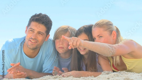 Cute family watching someone on a beach