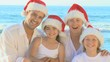 Family wearing  Christmas hats on a beach