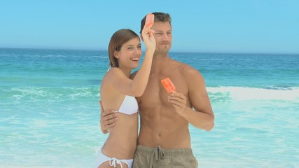 Beautiful couple eating orange water ices