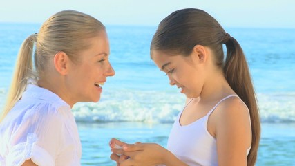 Girl putting suncream on her mother's face