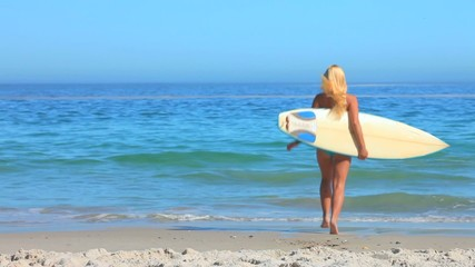 Blonde girl going surfing