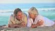 Elderly couple lying on a beach