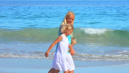 Blonde mother and her children having fun on a beach