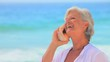 Elderly woman listening to a shell and smiling
