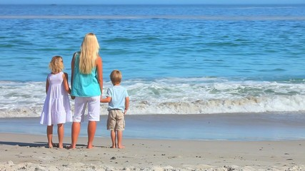 Blonde woman with son and daughter looking at the sea
