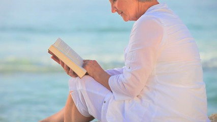 Mature woman sitting reading on a beach