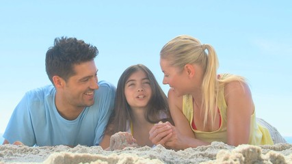 Happy parents and daughter lying on a beach