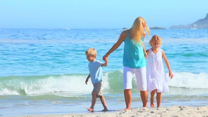 Beautiful blonde woman and children walking near the sea