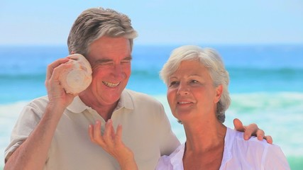 Mature couple listening to shell together