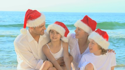 Cute family wearing Christmas hats on the beach