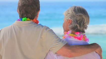 Elderly couple on the beach wearing garlands of flowers