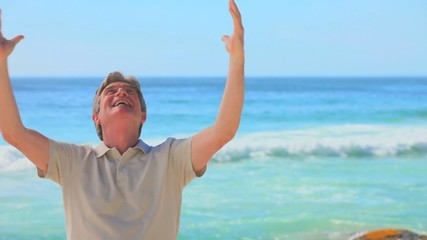 Elderly man on a beach expressing joy