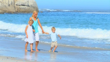 Cute young family walking on the beach