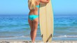 Blonde woman with surfboard looking at the sea