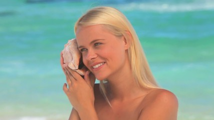 Blonde woman listening  to a shell