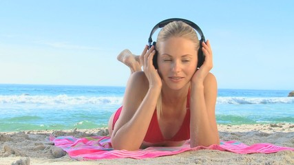 Blonde woman in a red swimsuit listening to music