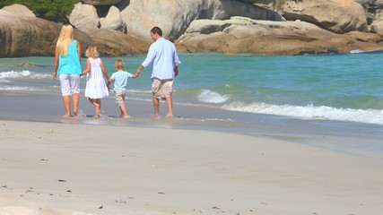 Happy family walking at the edge of the sea