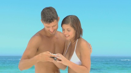 Beautiful couple taking photos on a beach