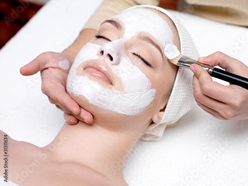 Fototapeta Woman receiving facial mask at beauty salon