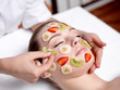Woman receiving fruit facial mask at spa salon