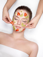 Woman getting fruit cosmetic facial mask