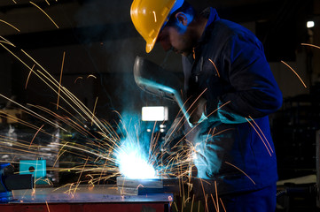 Worker making sparks while welding steel.