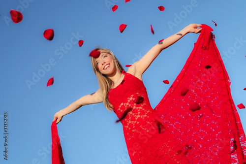 happy summer or spring girl with rose flower petals falling