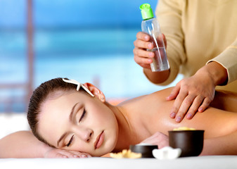 woman getting massage with cosmetic oil in spa salon