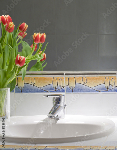 Working mixer tap with a few tulips on a counter