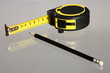 Tape measure and a pencil on neutral background