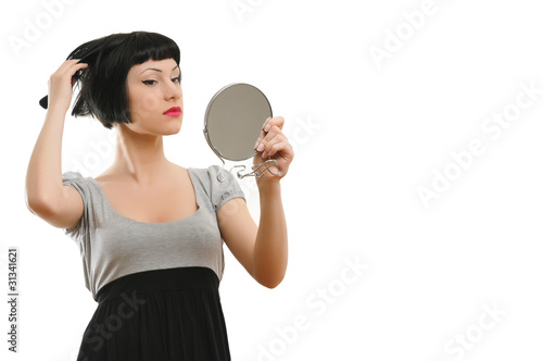 Portrait of a beautiful woman looking at the mirror