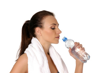 A young and sporty brunette woman is drinking fresh water