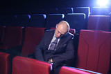 Bald man sleeping in empty cinema movie theater