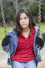 Angry, sad preteen girl sitting on swing