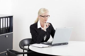 Frau am Schreibtisch sitzend mit Laptop