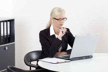 Frau am Schreibtisch mit Laptop im Businessoutfit