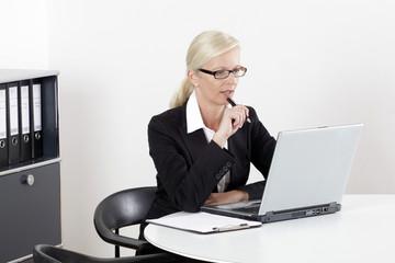 Frau am Schreibtisch mit Laptop und Stift
