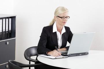 Frau am Schreibtisch mit Laptop schreibend