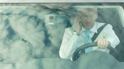 businessman driving car and talking on the phone