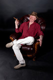 Senior man sitting in large leather armchair and smoking cigar