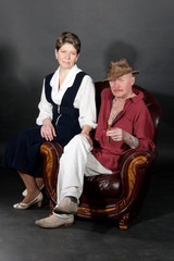 Mid-aged couple sitting in leather armchair