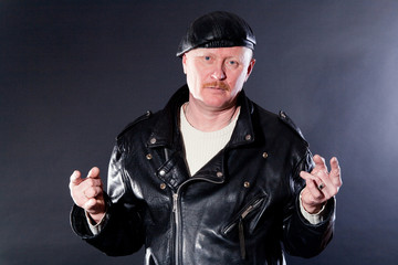 Middle-aged male dressed in leather posing as biker in studio