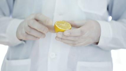 Scientist hands in rubber gloves examining lemon